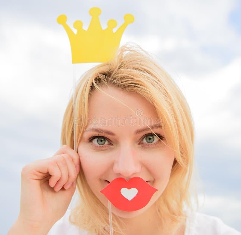 妇女金发举行纸板冠状头饰或冠和爱天空背景的红色嘴唇标志 每个女孩梦想  免版税库存图片