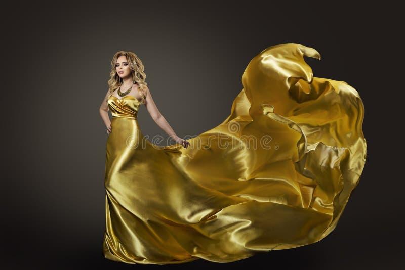 妇女金礼服,在长的丝绸褂子的时装模特儿跳舞 免版税库存图片