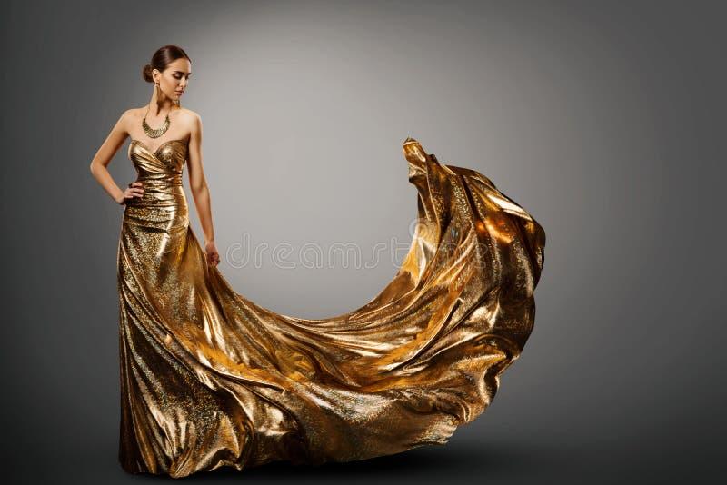 妇女金礼服,在长的挥动的褂子的时装模特儿,少女秀丽 免版税库存照片