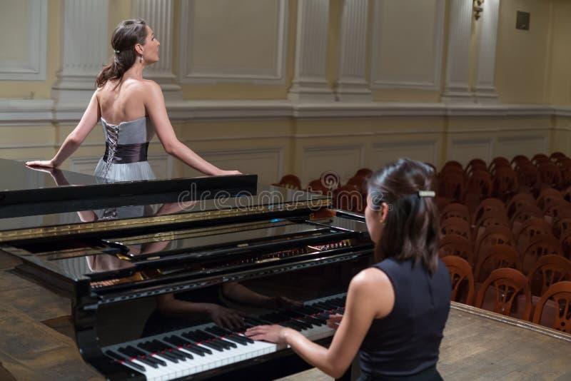 妇女钢琴演奏家坐在钢琴和美丽的歌手 免版税库存图片