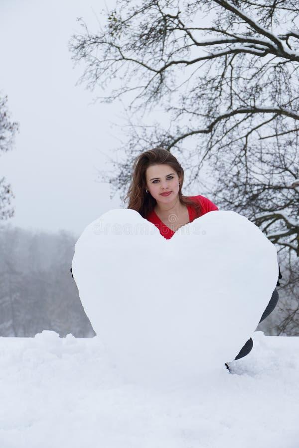 妇女铸造雪的心脏 免版税库存照片