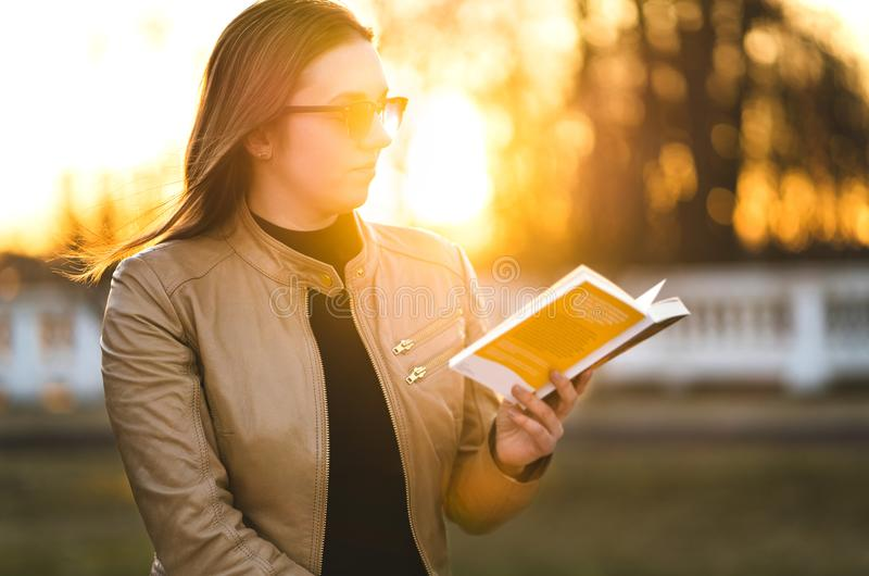 妇女阅读书外面在公园 享用小说的夫人户外 免版税图库摄影