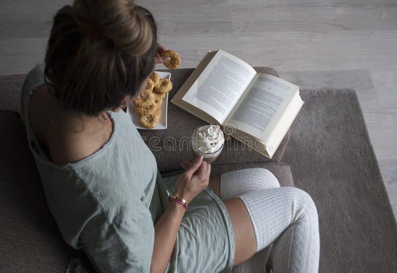 妇女阅读书顶视图在家在长沙发用热巧克力牛奶和曲奇饼 免版税库存照片