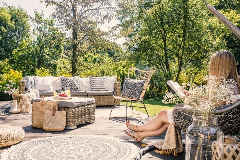 妇女阅读书,当放松在与藤条furnitu时的大阳台 库存照片