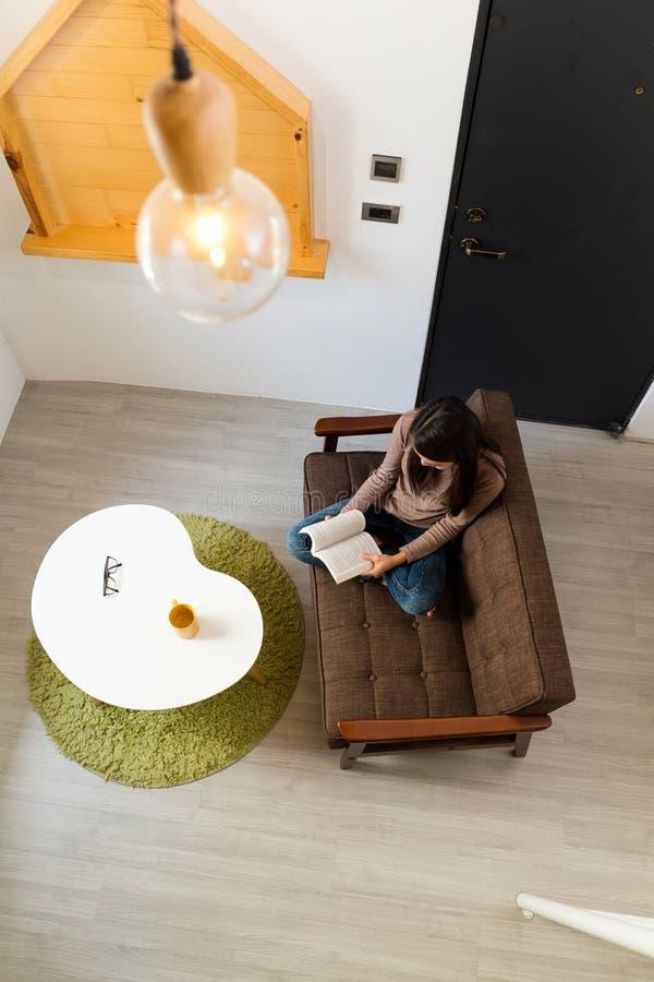 妇女阅读书和开会顶视图在沙发 库存图片