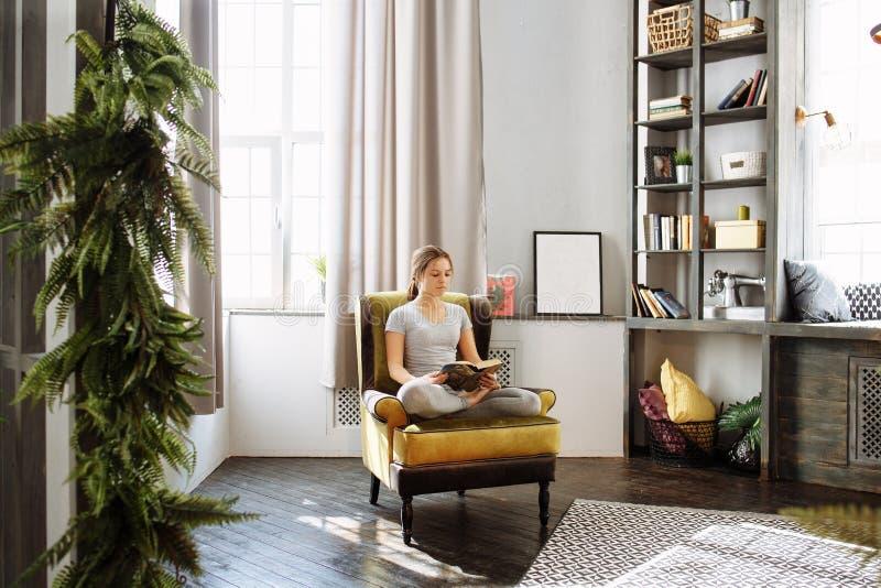 妇女阅读书在家在客厅 免版税图库摄影