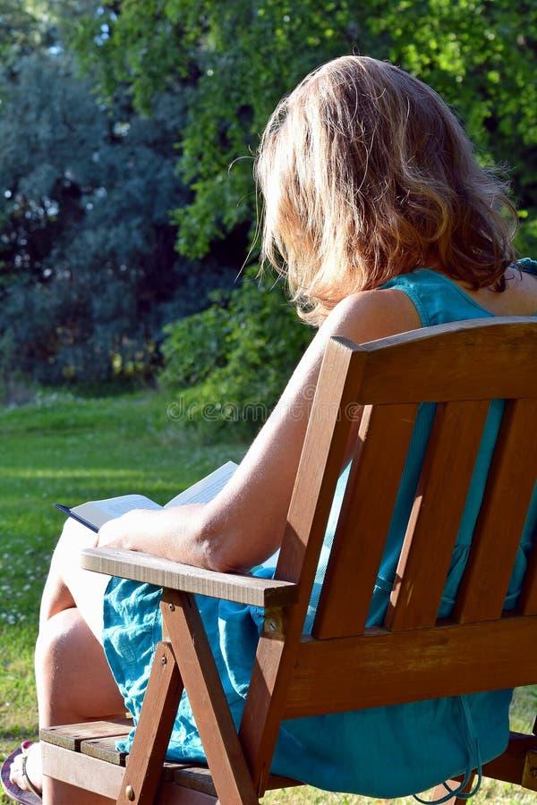 妇女阅读书在庭院里 免版税图库摄影
