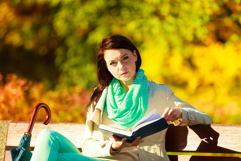 妇女阅读书坐长凳在公园 免版税库存图片