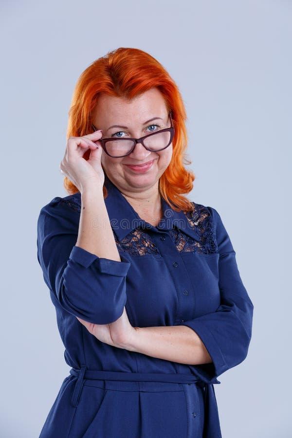 妇女降低了她的与微笑的玻璃并且直接地注视着特写镜头灰色背景 免版税库存照片