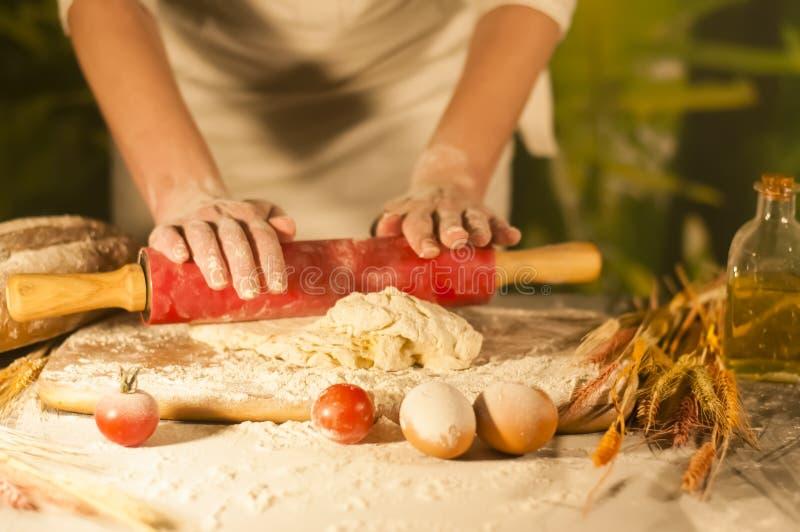 妇女面包师手面团黄油厨师蕃茄酵母成份准备面团和制造面包 库存照片