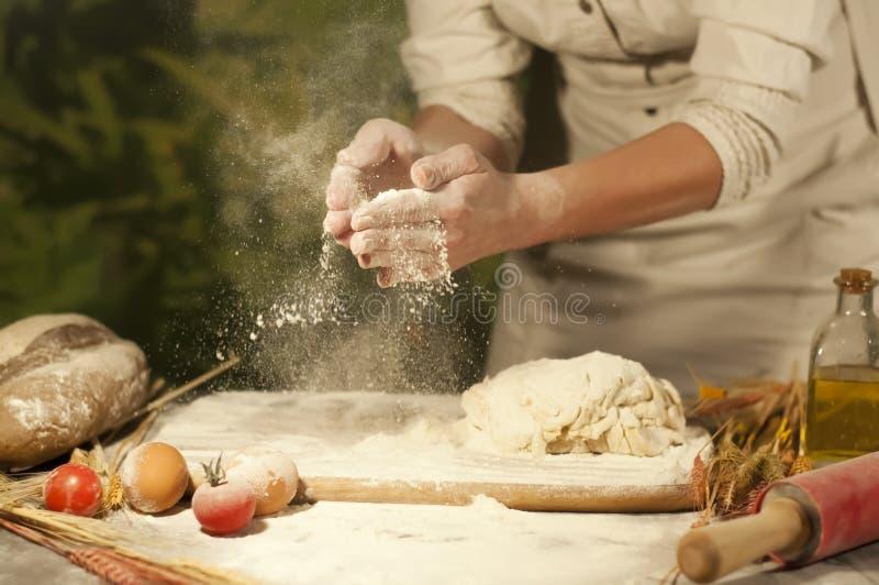 妇女面包师递,揉面团和做做面包,黄油,蕃茄面粉 免版税库存图片