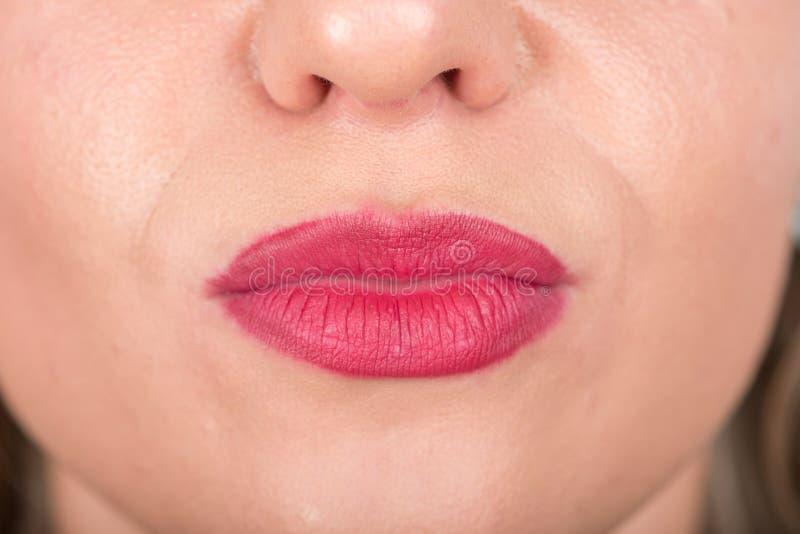 妇女面孔和亲吻标志与嘴唇 演播室照片写真 使用明亮的红色唇膏 库存照片