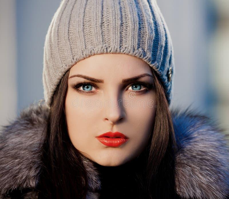 妇女面孔皮大衣和灰色帽子,蓝色骗局 库存照片