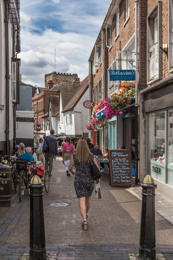 妇女顾客步行沿着向下通过咖啡馆和室外吃饭的客人的历史的法国行 免版税库存图片