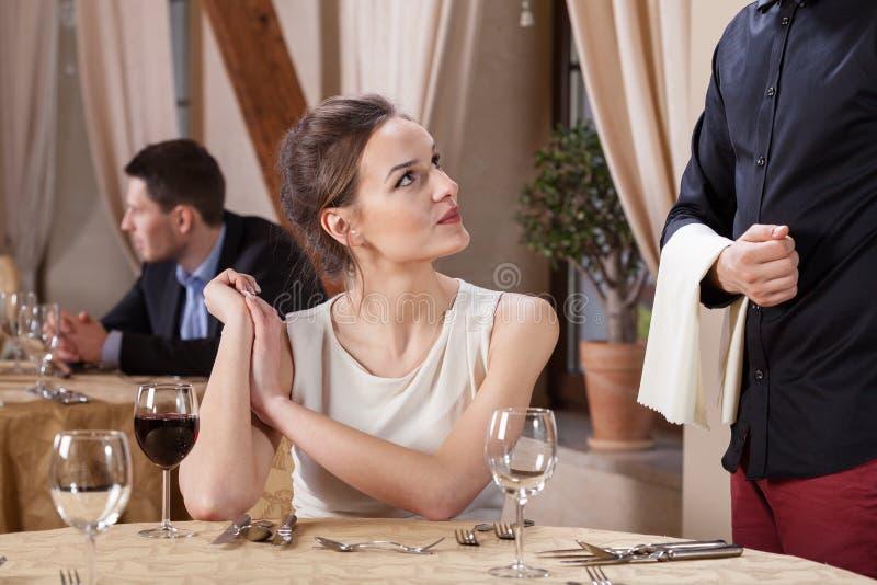妇女预定的膳食在餐馆 库存图片