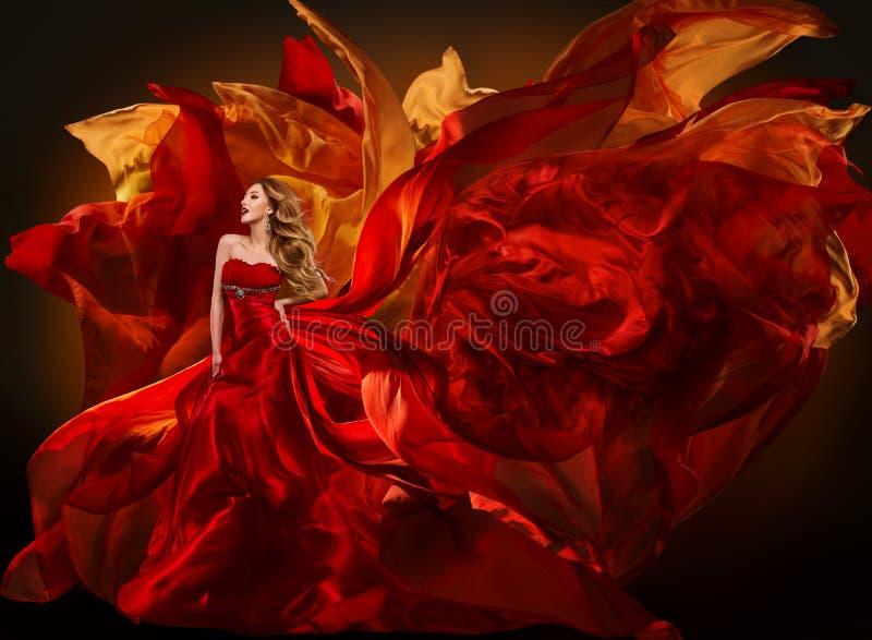 妇女飞行红色织品,女孩挥动的丝绸布料的时尚礼服 免版税库存照片