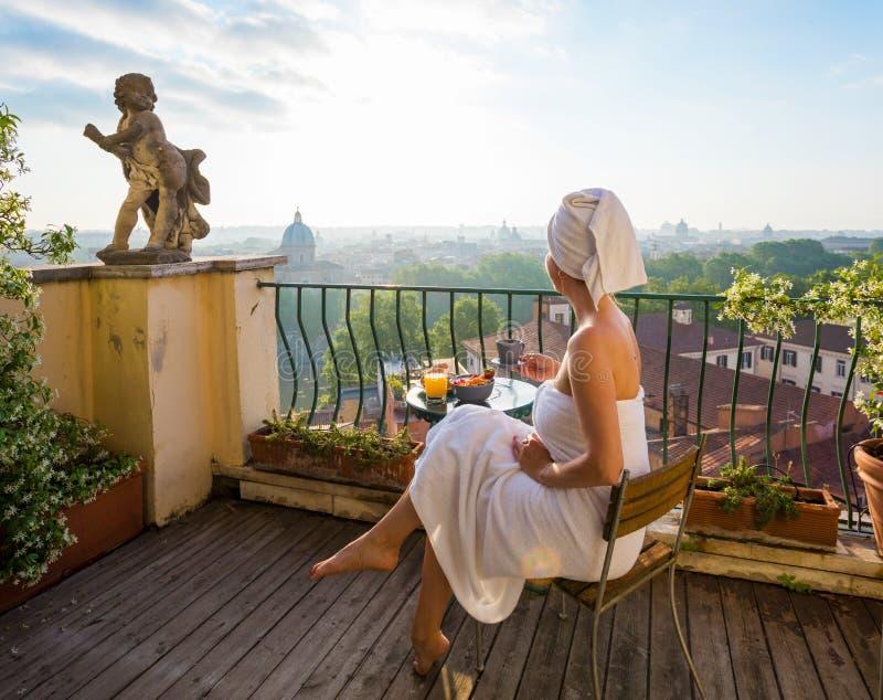 妇女食用在阳台的早餐在城市 免版税库存图片