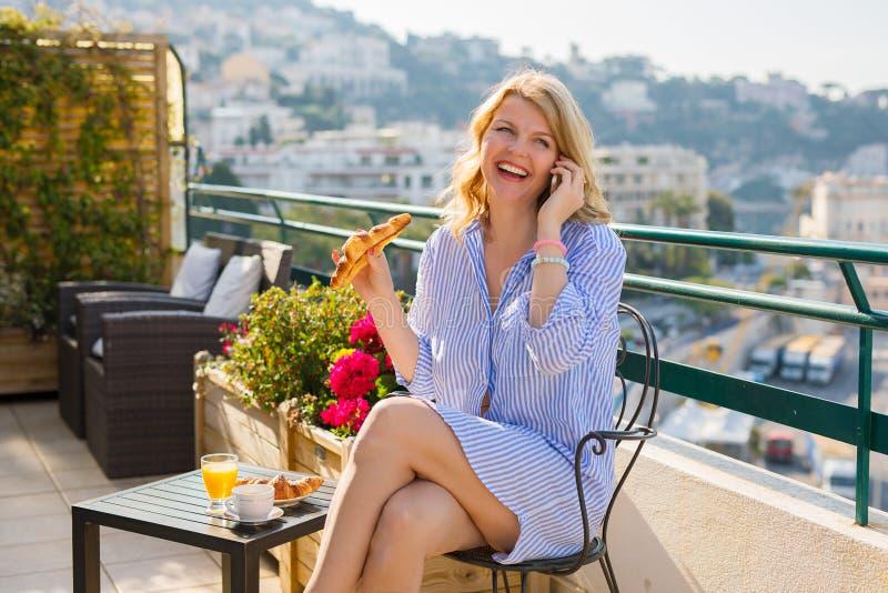 妇女食用早餐户外和发表演讲关于手机 免版税库存图片