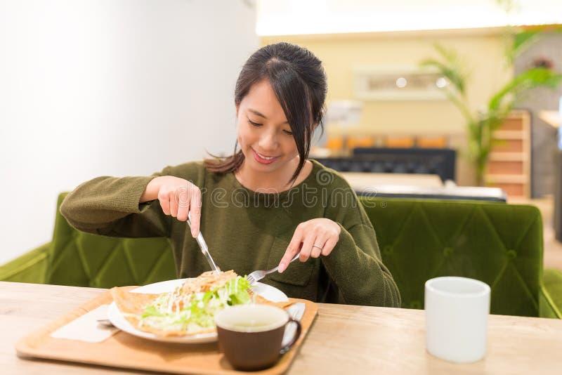 妇女食用薄煎饼在餐馆 库存图片