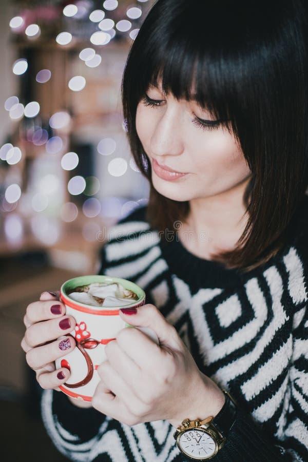 妇女饮料可可粉用在xmas前面的蛋白软糖点燃 图库摄影
