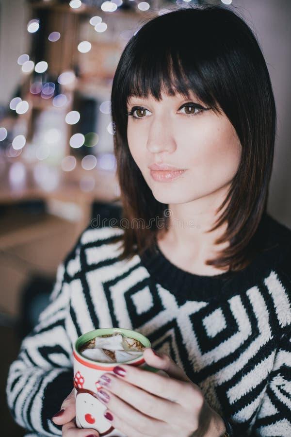 妇女饮料可可粉用在xmas前面的蛋白软糖点燃 库存照片