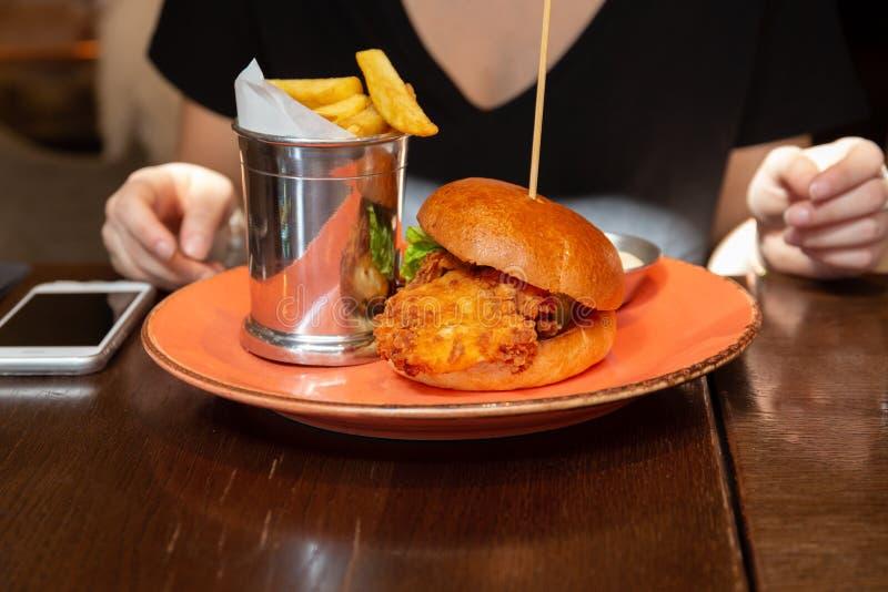 妇女饮用与芯片的一个可口酥脆鸡汉堡在午饭时间 库存图片