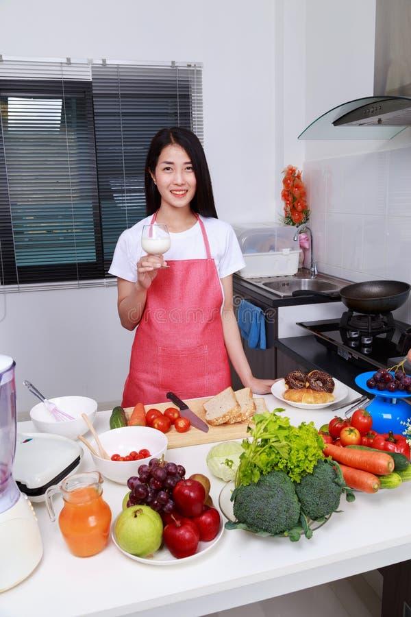 妇女饮用奶在厨房屋子里 免版税库存图片
