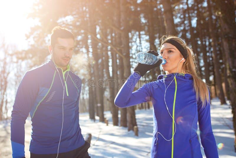 妇女饮用水在训练的森林 免版税库存图片
