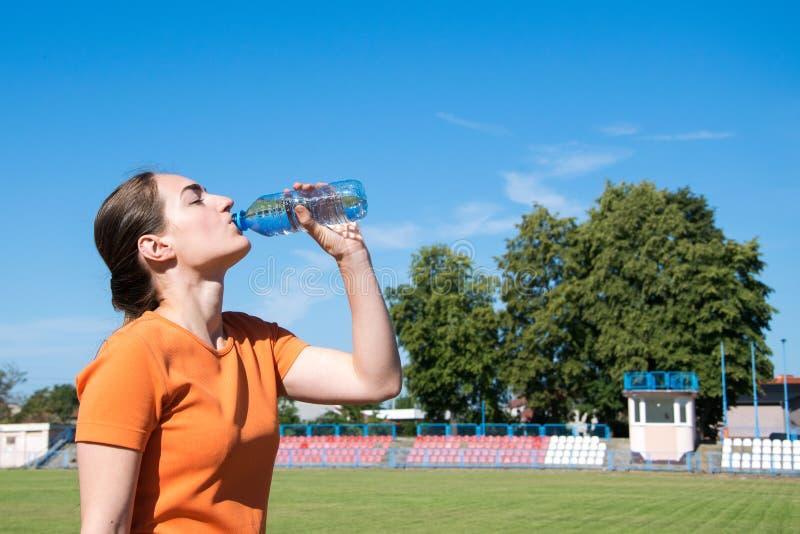 妇女饮用水在跑步以后 免版税库存照片