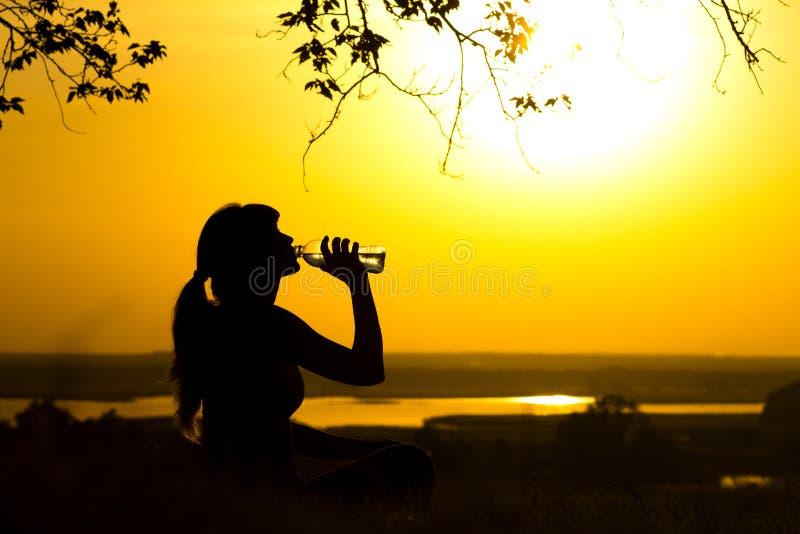 妇女饮用水的剪影在健身训练本质上,女性体育的外形在日落,概念和放松以后的 免版税库存照片