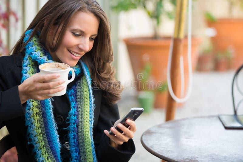 妇女饮用的咖啡发短信 免版税库存照片