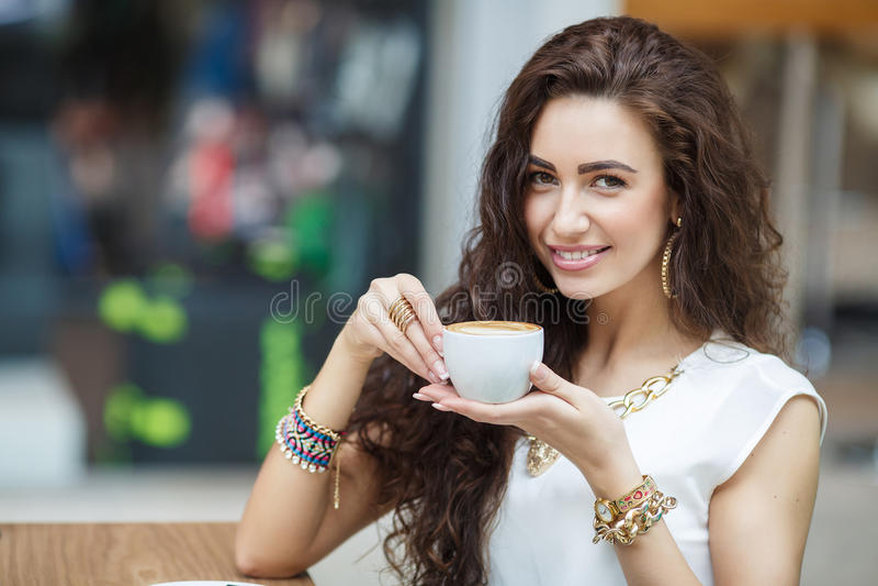妇女饮用的咖啡在家,与日出 免版税库存图片