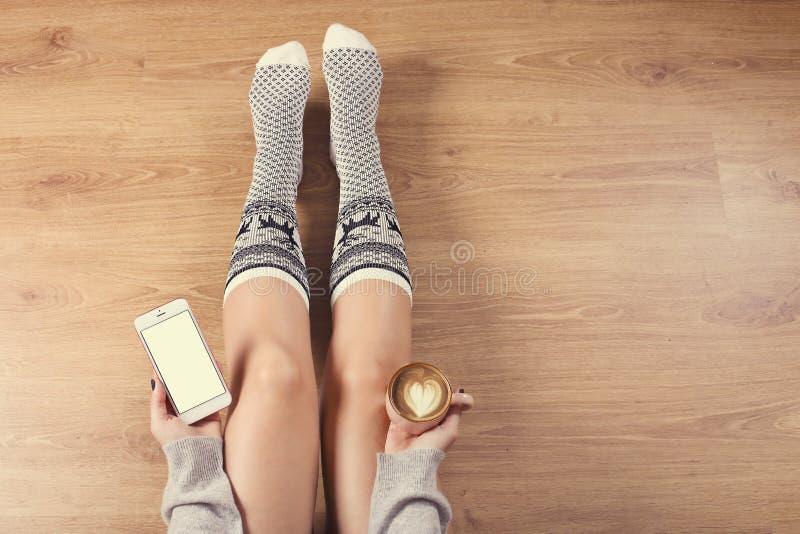 妇女饮用的热奶咖啡咖啡和坐木地板 关闭妇女拿着咖啡和使用的` s手聪明 免版税库存照片