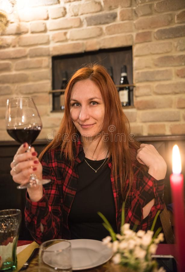 妇女饮用的酒在餐馆 免版税库存图片