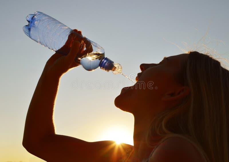 妇女饮用水的剪影从瓶的 库存照片