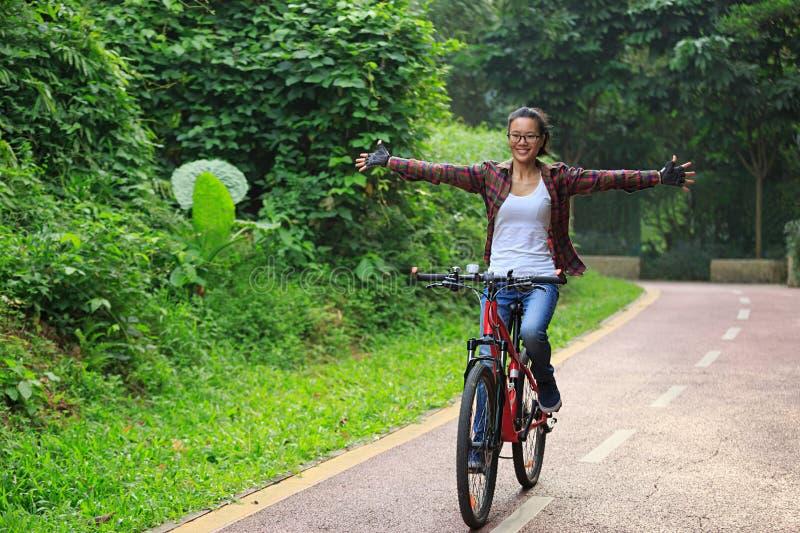 妇女骑自行车者乐趣在森林足迹的骑马自行车 免版税库存图片