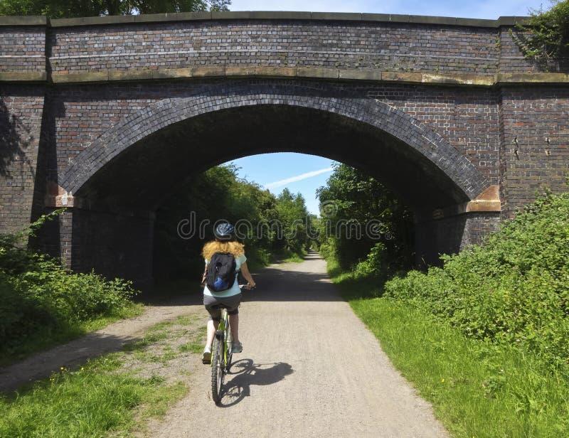 妇女骑自行车Wirral方式,西部柯尔比 免版税库存照片