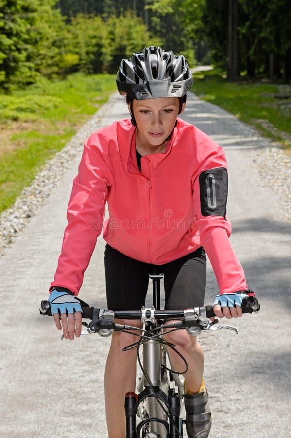 妇女骑马登山车晴朗的乡下道路 免版税库存照片