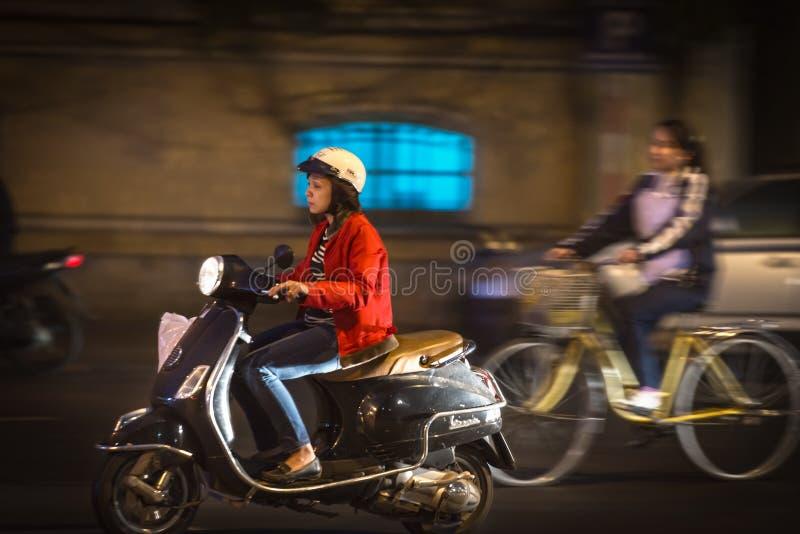 妇女骑马滑行车在晚上在越南,亚洲。 免版税库存图片