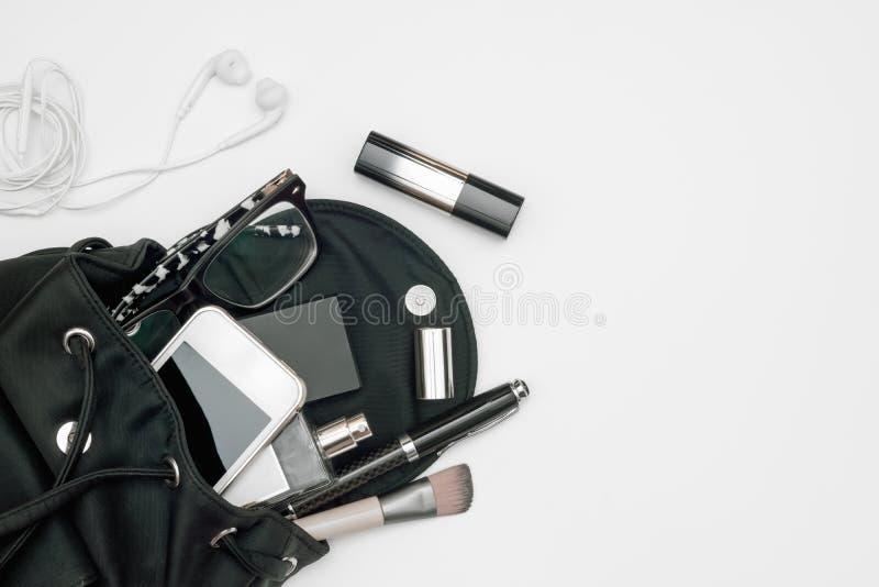 妇女黑色袋子顶视图开放与在白色的辅助部件智能手机、香水、笔、化妆用品、耳机和玻璃 库存照片