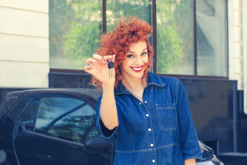 妇女,在她给钥匙的新的汽车陈列附近的买家 免版税库存照片