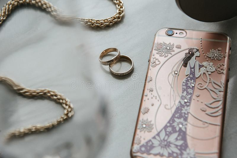 妇女\'s辅助部件是在桌上 链子,电话,圆环在桌上 免版税库存照片