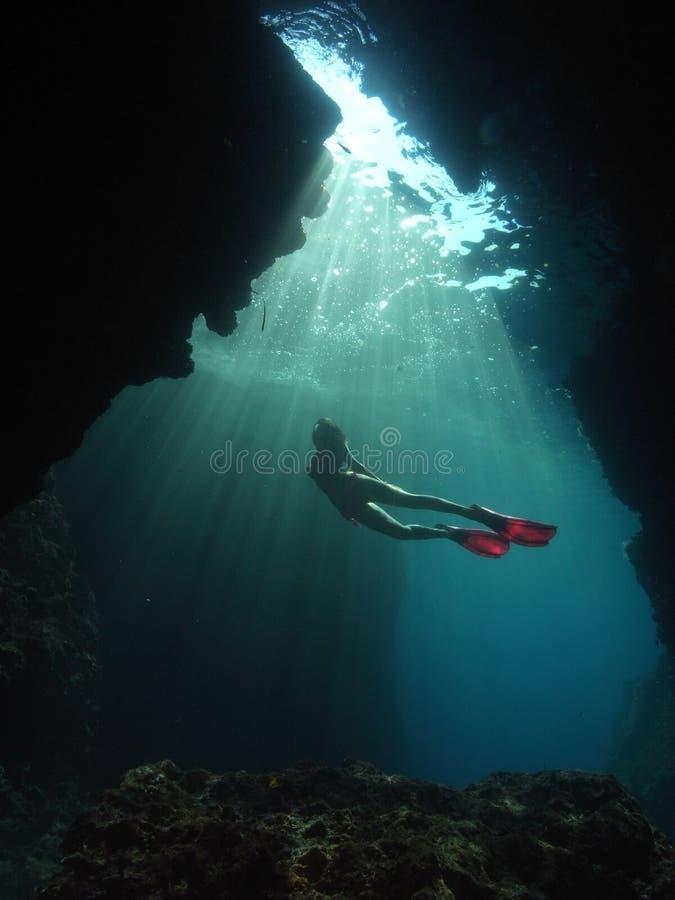 妇女水下的摄影师佩戴水肺的潜水洞 免版税库存图片