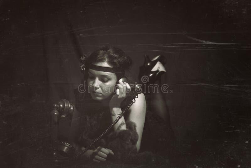 妇女20世纪20年代样式腹部downwith老电话 葡萄酒样式photog 免版税图库摄影