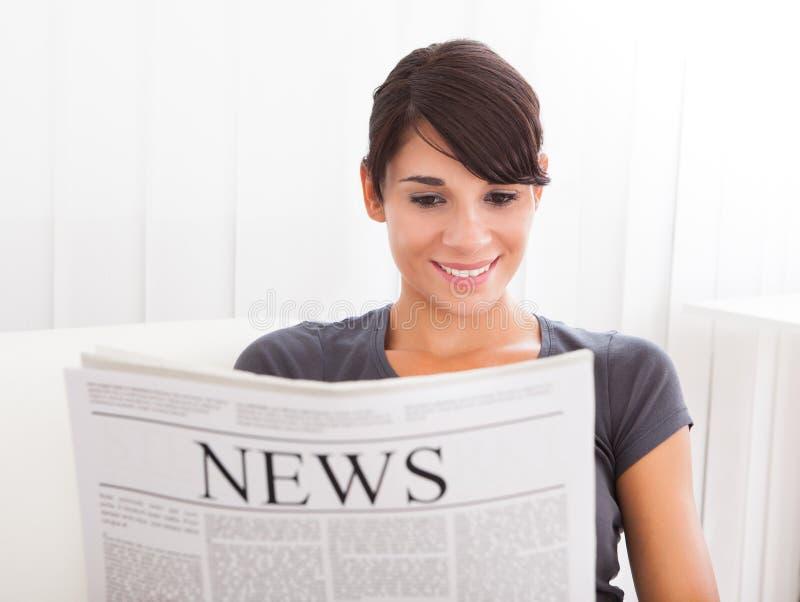 妇女读书报纸 免版税图库摄影