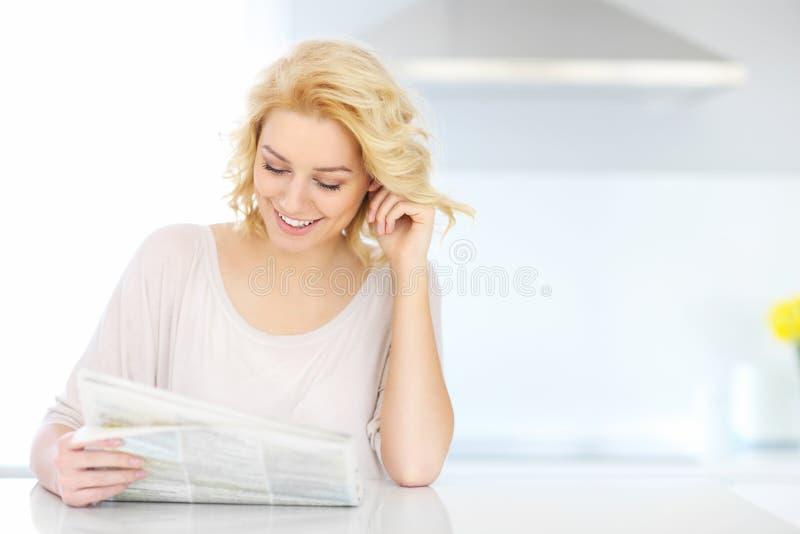 妇女读书纸早晨 免版税库存图片