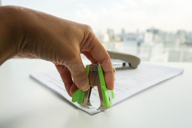妇女从商业文件的拉扯钉书针由钉书针去膜剂 库存照片
