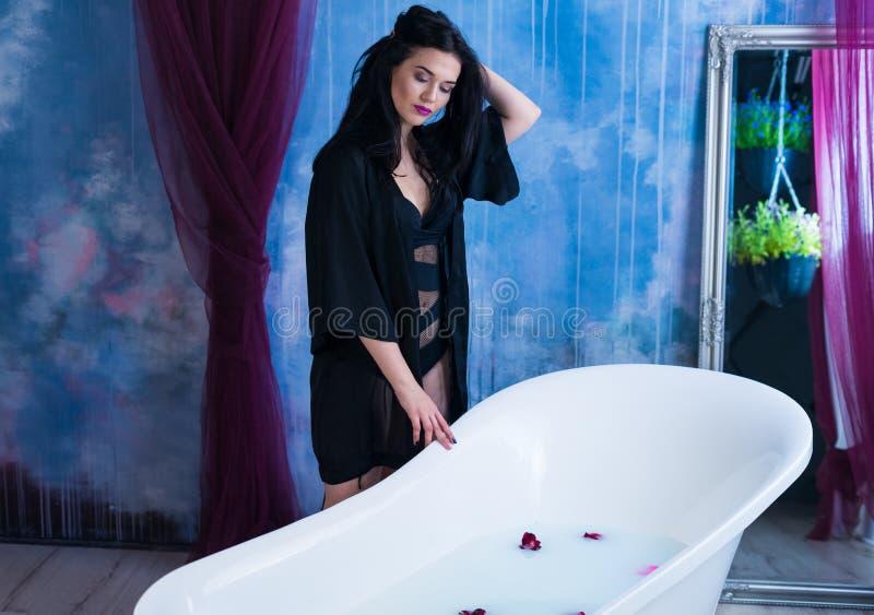 浴妇女 在去的性感的深色的妇女bathtube前用牛奶 免版税库存照片