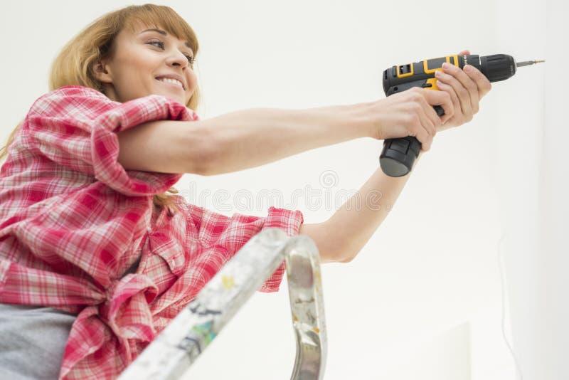 妇女钻墙壁在新房里 库存照片
