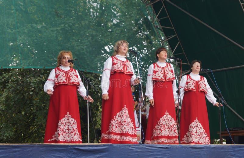 妇女(妇女)在全国衣服的s在场面唱歌 免版税库存图片